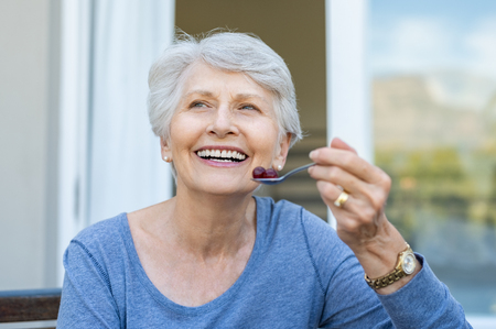 Cheerful senior woman holding red grapes in spoon and make a beautiful white smile. Smiling old woman looking away while eating fresh fruits for breakfast. Mature woman enjoying old age and healthy eating. Archivio Fotografico