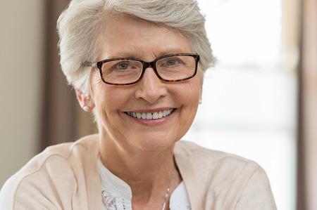 Portrait d'une femme senior heureuse portant des lunettes. Belle femme âgée avec des lunettes souriant à la maison. Femme mature aux cheveux gris portant des spécifications tout en regardant la caméra. Banque d'images