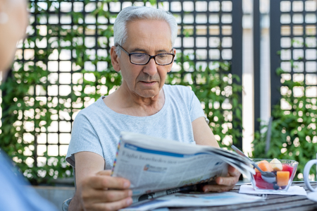 Elderly man with eyeglasses reading an article in the newspaper. Senior man with serious expression reading news while sitting at breakfast table. Mature man reads bad news on paper. Banco de Imagens