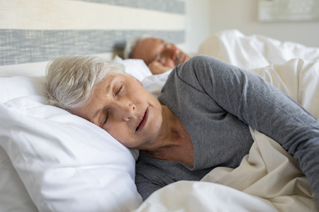 Old woman sleeping on bed at home with her husband. Elder lady sleeping in the bedroom with husband in background. Senior woman with grey hair wearing nightwear asleep in bed.