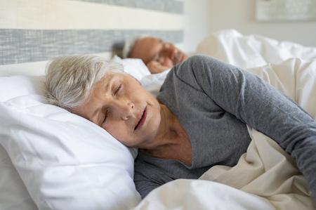 Vieille femme endormie sur le lit à la maison avec son mari. Dame aînée dormant dans la chambre avec son mari en arrière-plan. Senior femme aux cheveux gris portant des vêtements de nuit endormie dans son lit.