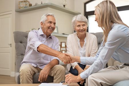 Felice coppia senior di tenuta con stretta di mano un contratto per il pensionamento. Uomo in pensione soddisfatto sorridente che fa l'affare di acquisto di vendita che conclude con una stretta di mano. Uomo anziano e donna che sorridono mentre sono d'accordo con il consulente finanziario.