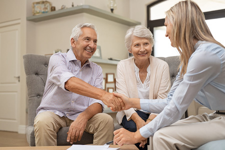 Glückliches älteres Paar, das mit Händedruck einen Vertrag für den Ruhestand besiegelt. Lächelnder zufriedener pensionierter Mann, der Verkaufskaufabkommen macht, das mit einem Handschlag abschließt. Älterer Mann und Frau lächeln, während sie mit Finanzberater übereinstimmen.