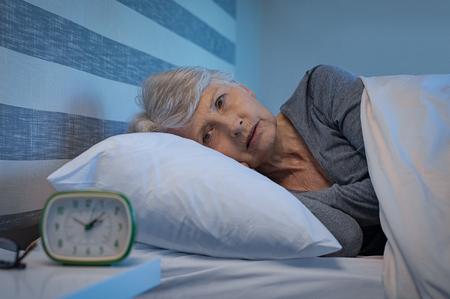 Bezorgd senior vrouw in bed 's nachts die lijdt aan slapeloosheid. Oude vrouw liggend in bed met open ogen. Rijpe vrouw die thuis niet kan slapen.