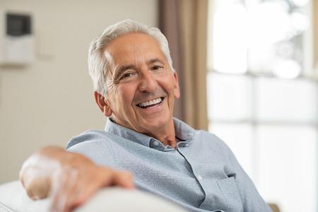 Portret van gelukkig senior man die lacht thuis. Oude man ontspannen op de bank en camera kijken. Portret van oudere man die van pensionering geniet.