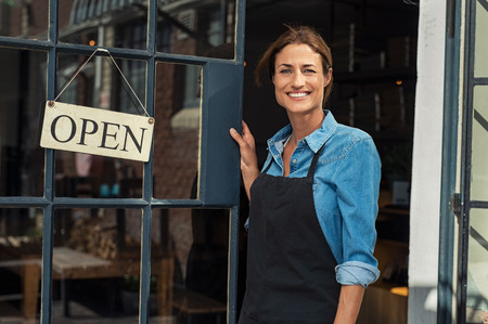 Portrait of a happy waitress standing at restaurant entrance. Portrait of mature business woman in black apron ready to attend new customers in her just opened coffee shop. Happy beautiful woman owner showing open sign in her small business shop. Stock Photo