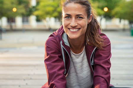 Portrait of smiling woman sitting on floor of city street after running. Healthy mature runner resting after workout exercise and looking at camera. Active latin sporty woman enjoying outdoors in autumn.