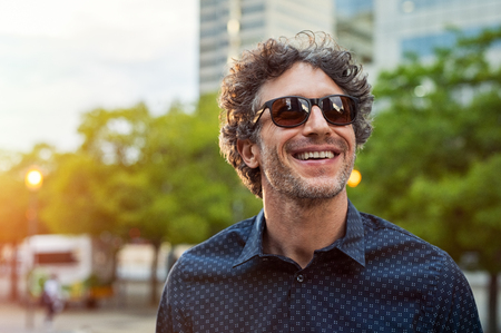 Portrait of smiling man wearing sunglasses and looking away in the city streets. Cheerful mature businessman walking with a big smile on face. Happy man in blue shirt and glasses enjoying the sunset. Banco de Imagens