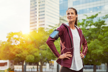 Latin sport woman listening music with earphones while standing and resting after running outdoors. Mature woman wearing jacket and standing after morning run in urban city. Satisfied runner looking away with pride.