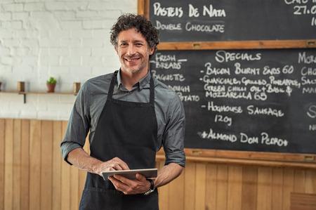 Reifer Kellner, der schwarze Schürze trägt und mit der Tageskarte vor der Tafel steht. Porträt des lächelnden Mannes, der digitales Tablett hält und Kamera betrachtet. Glücklicher Kleinunternehmer, der in der Cafeteria mit digitalem Tablett arbeitet.
