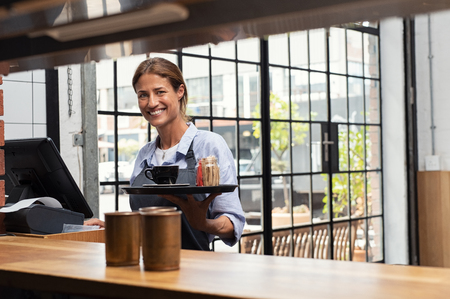 Smiling waitress serving cup of coffee in restaurant. Happy woman holding tray with cappuccino at the coffee shop and preparing bill while looking at camera. Beautiful woman holding tray with coffee making cheque for customer.