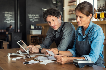 Man and woman sitting in cafeteria discussing finance for the month. Stressed couple looking at bills sitting in restaurant wearing uniform apron. Café staff sitting together looking at expenses and bills. Stock Photo