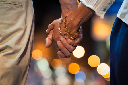 Closeup of loving couple holding hands while walking outdoors at night. Mature man and fashionable woman holding hands while walking on street at night. Hands of senior married couple joined together, romantic atmosphere.