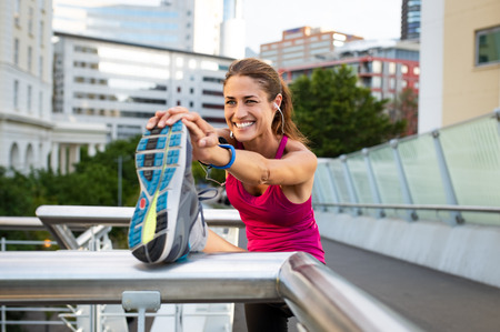 Smiling mature woman doing stretching with her leg raised. Fitness woman listening to music with earphones while stretching leg in the city. Beautiful runner warming up.