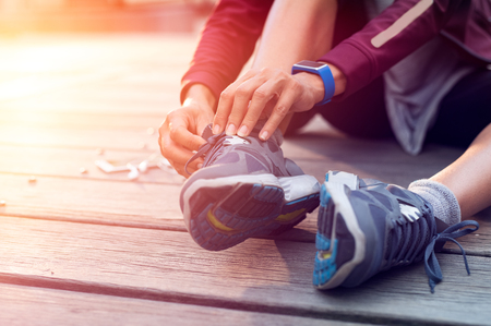 Closeup hand of runner tying laces of her sport shoes. Woman sitting on floor and lacing training sneakers before getting ready for workout.Hands of sportswoman tying shoelaces on sporty sneaker. Stockfoto