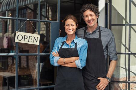 Twee vrolijke eigenaren van kleine bedrijven glimlachen en kijken naar de camera terwijl ze bij de ingangsdeur staan. Gelukkig volwassen man en medio vrouw bij ingang van nieuw geopende restaurant met open bord. Glimlachend paar gastvrije klanten naar kleine zakelijke winkel.