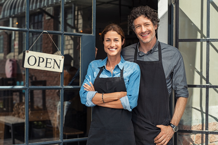 Two cheerful small business owners smiling and looking at camera while standing at entrance door. Happy mature man and mid woman at entrance of newly opened restaurant with open sign board. Smiling couple welcoming customers to small business shop. Stockfoto