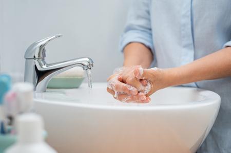 Primo piano della donna che applica sapone mentre si lavano le mani nel bacino con rubinetto aperto. Donna matura lavarsi le mani per scopi di pulizia. Signora che sfrega le mani piene di sapone. Archivio Fotografico