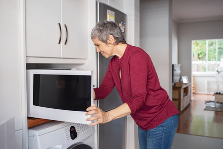 Senior woman keeping food in oven for heating.