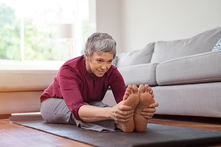 Mooie senior vrouw stretching oefening zittend op yoga mat thuis.