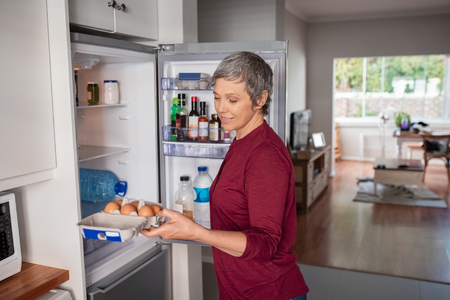 Senior woman removing eggs tray from refrigerator to prepare a pie.