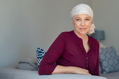 Mature woman with cancer in pink headscarf smiling sitting on couch at home.