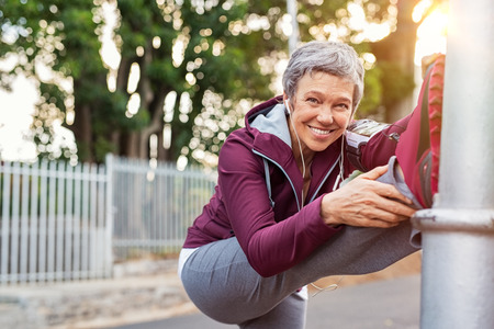 Smiling retired woman listening to music while stretching legs outdoors.