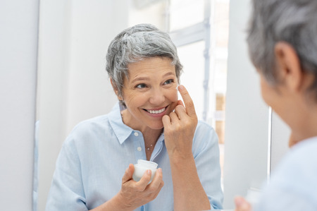 Happy mature woman applying face lotion while looking herself in the bathroom mirror. Senior woman applying anti aging moisturizer on her face. Smiling lady holding little jar of skin cream and applying lotion during the morning routine. Stock Photo