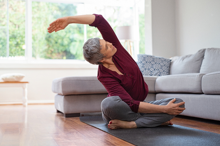 Senior woman exercising while sitting in lotus position. Active mature woman doing stretching exercise in living room at home. Fit lady stretching arms and back while sitting on yoga mat. Stock Photo