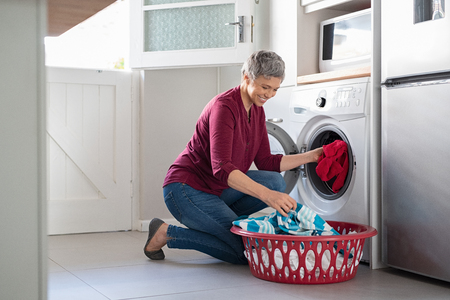 Happy senior woman loading dirty clothes in washing machine. Smiling mature woman sitting on floor putting clothed in washing machine from laundry basket. Housework.