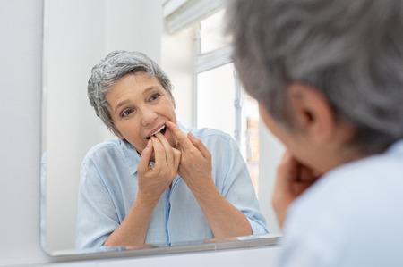 Hermosa mujer madura limpiando sus dientes con hilo dental en el baño.