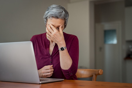 Mature businesswoman suffering a stress headache sitting at her desk with closed eyes in pain.