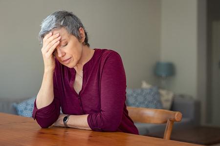 Senior vrouw die lijden aan hoofdpijn zittend aan tafel in een woonkamer.