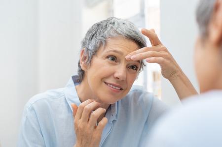 Donna matura che osserva il suo viso e le rughe nello specchio del bagno. Archivio Fotografico