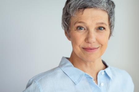 Nahaufnahmegesicht der älteren Geschäftsfrau, die gegen grauen Hintergrund mit Kopienraum steht. Standard-Bild