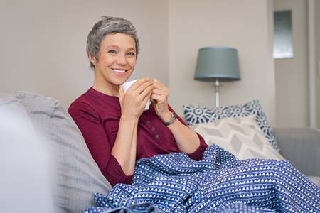 Portrait of smiling senior woman drinking coffee at home while looking at camera.