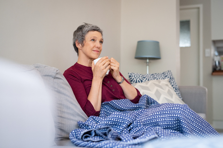 Relaxed mature woman enjoying tea sitting with blanket on a comfortable couch.