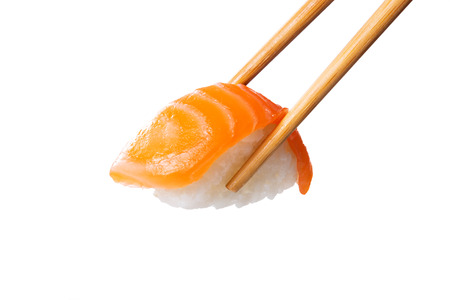 Closeup of salmon nigiri held with bamboo chopsticks. Fresh sushi nigiri isolated on white background. Eating sushi at restaurant. Japanese cuisine with rice and raw fish.