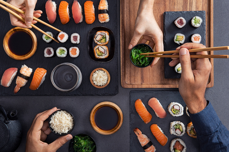 Top view of couple hands eating sushi food at japanese restaurant. High angle view of woman hand serving seaweed in little bowl with sesame to man while holding hosomaki with chopsticks. Couple eating and sharing sushi roll, maki, nigiri, uramaki. Stock Photo