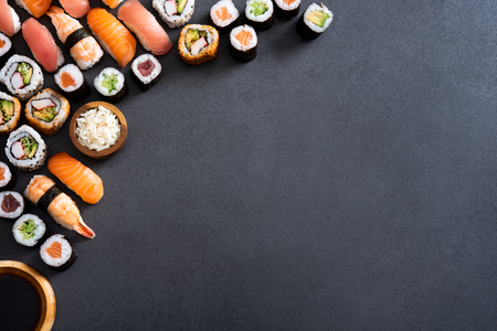 Top view of corner of hosomaki, uramaki, nigiri and soy sauce on blackboard. High angle view of fresh maki rolls and wooden bowl of rice on slate stone. Variety of sushi pieces on stone table with copy space.