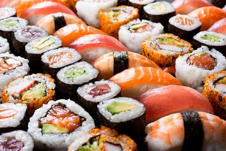 Cibo di sushi giapponese in testa. Maki ands roll con tonno, salmone, gamberi, granchio e avocado. Vista dall'alto di sushi assortito, tutto ciò che puoi mangiare menu. Rotolo di sushi arcobaleno, uramaki, hosomaki e nigiri. Archivio Fotografico