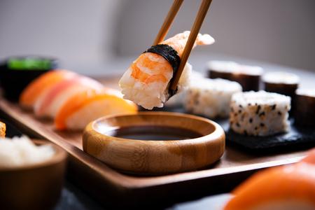 Close-uphand die bamboestokjes met nigirigarnalen houdt terwijl het in sojasaus wordt geweekt. Detail van sushi op houten dienblad in restaurant terwijl hand nigiri in sojasaus dompelt. Japans keukenconcept.