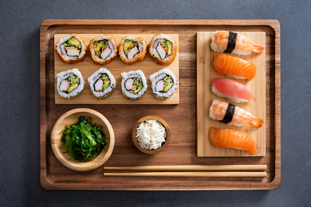 Top view of delicious variety sushi pieces setting on wooden tray. High angle view of japanese food with huramaki, maki, rolls, nigiri, seaweed and rice in a bowl. Flat image of fresh japanese sushi served on bamboo tray with chopstick on slate table. 版權商用圖片