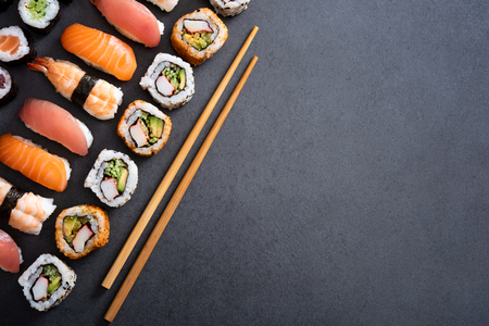 Top view of sushi with bamboo chopstick on black background. High angle view of corner of fresh uramaki, nigiri and hosomaki on blackboard with copy space. Japanese food with fish rolls and spicy maki on slate with wooden chopstick.