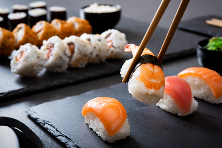 Shrimp sushi nigiri on a black plate with wooden chopsticks. Closeup of nigiri set with chopsticks and soy sauce with uramaki and hosomaki in background. Eating japanese food on black slate dishes at restaurant. Stock Photo