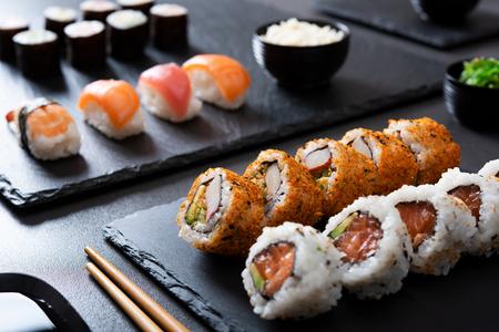 Japanese sushi food served on blackboard plate with bowl of rice and seaweed. Sushi roll with prawn, avocado, cream cheese, sesame. Uramaki, hosomaki rolls and nigiri on black table with chopstick.