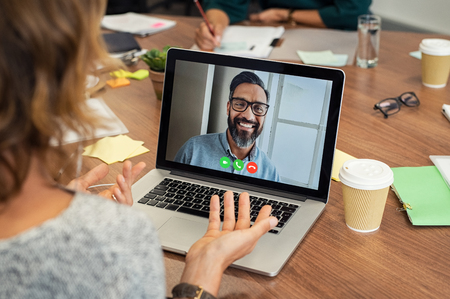 Portrait of smiling man video conferencing on laptop with businesswoman. Casual woman video conferencing with mature middle eastern businessman on laptop. Happy man in video call with colleague over laptop. Stock Photo