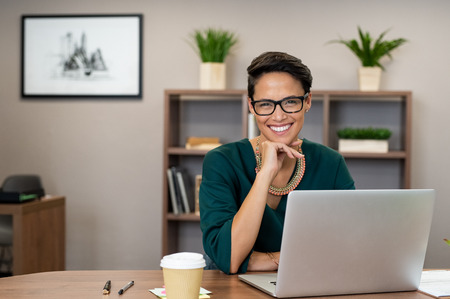 Portrait of happy casual businesswoman sitting at her desk in office. Cheerful latin woman working on laptop and looking at camera. Young fashionable girl wearing eyeglasses sitting at creative agency.