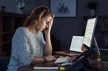 Donna d'affari matura e stanca che lavora in ufficio fino a notte. Ritratto di una signora stressata casual con mal di testa alla scrivania vicino al computer desktop. Donna d'affari esaurita che lavora a tarda notte al computer in ufficio.