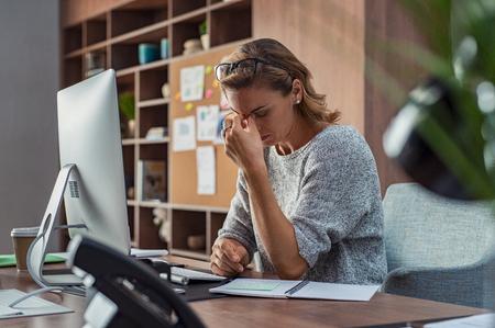 Donna d'affari esaurita che ha mal di testa in un ufficio moderno. Donna creativa matura che lavora alla scrivania dell'ufficio con gli occhiali sulla testa sentendosi stanca. Donna d'affari casual stressata che sente dolore agli occhi mentre lavora troppo sul computer desktop. Archivio Fotografico